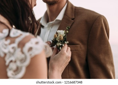 bride fastens a buttonhole, groom's boutonniere
