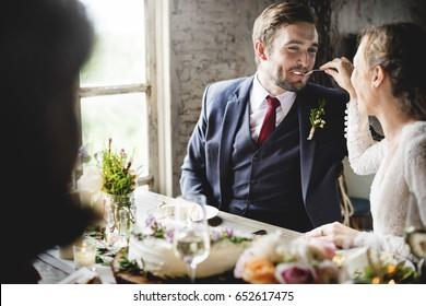 Bride Feeding Cake to Groom on Wedding Reception Happiness