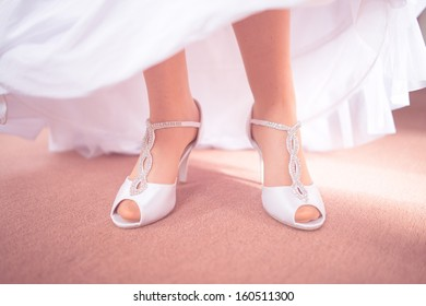Bride fitting shoes on her wedding day