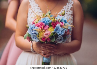 bride with flowers in hand outdoors. Blonde woman in wedding dress.
