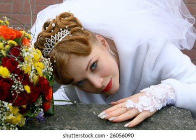 Bride with flowers on the stone wall