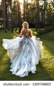The bride in a flying dress of a gray-blue color runs in the evening sun. Around the forest, pine, green grass.