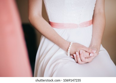 Bride folded her hands on the knees in expectation of groom. bride's morning