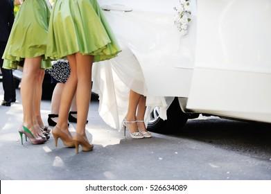 bride getting into car with bridesmaids around, happy wedding day