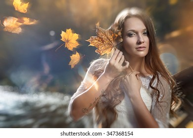 The bride, a girl with autumn leaves in the hands. The bride, portrait, beauty.