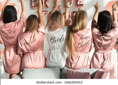 Bride with girlfriends in silk robes at a bachelorette party.