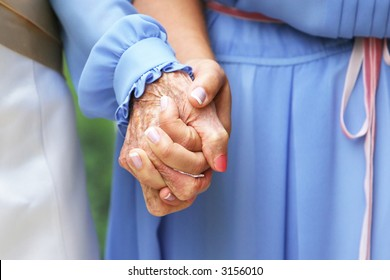 Bride and grandmother hold hands on wedding day