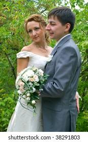 bride and groom against summer landscape