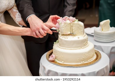 The bride and groom at the banquet together cut the wedding cake, holding on to one knife. Wedding details close-up