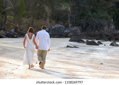 The bride and groom barefoot walking on the sandy beach the quiet