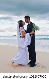 The bride and groom are at the beach in hawaii. a cloudy sky and a romantic moment
