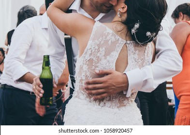 The bride and groom with a beer in their hands, hugging after their first dance as hunters