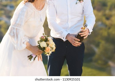 bride and groom with bottle of champagne at sunset