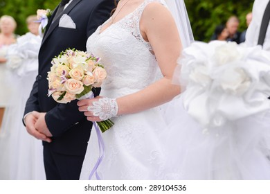 the bride and groom with a bouquet and holding hands each other