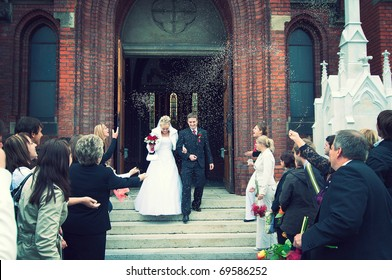 Bride and Groom at church door with rice confetti being thrown
