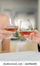 bride and groom clanging glasses with cognac