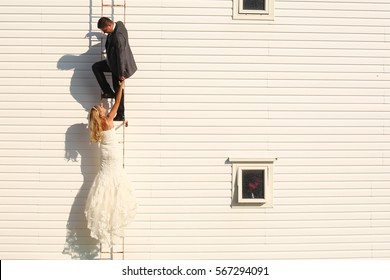 bride and groom climbing on a white house
