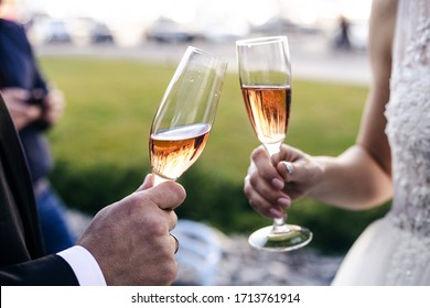 The bride and groom clink glasses with glasses. Effervescent wine or champagne is poured into the glasses. Shallow depth of field.