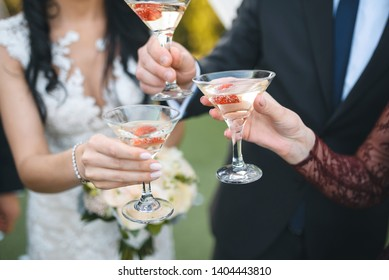 bride and groom clinking glasses with bridesmaid