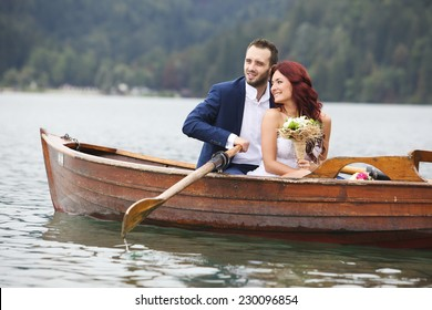Bride and groom close together in the lake rowing boat