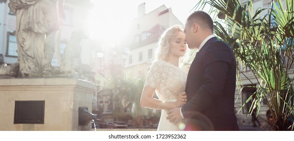 Bride and groom. Close-up portrait of a man in a suit and a woman with blond hair in a white dress on the wedding day.