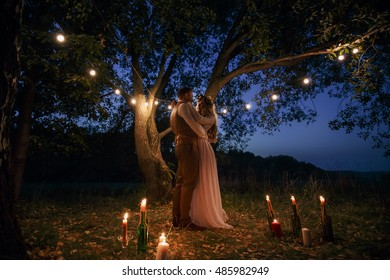 The bride and groom cuddling in the night standing at the tree. Night wedding ceremony.