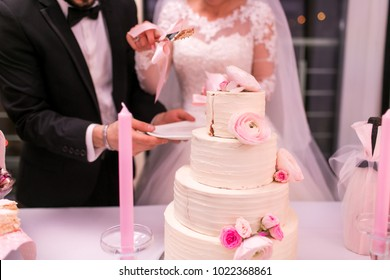 bride and groom cut a pink wedding cake