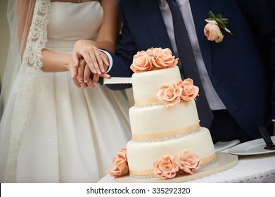 bride and groom cut the wedding cake. The cake is decorated with beige and peach-colored roses. groom is dressed in blue wedding suit and bride in a white wedding dress.