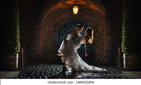 a bride and groom is dancing happily in the rain