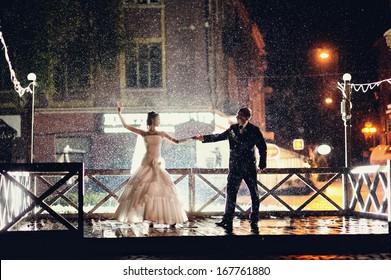 Bride and groom dancing in the night under rain