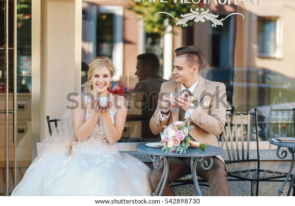 the bride and groom drinking coffee in a cafe
