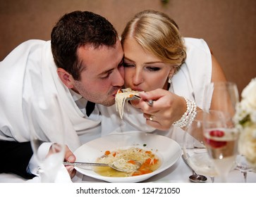 Bride and groom are eating at the wedding reception
