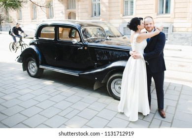 The bride and groom embracing near car