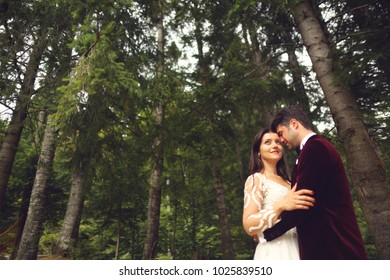 bride and groom embracing on a background of the forest