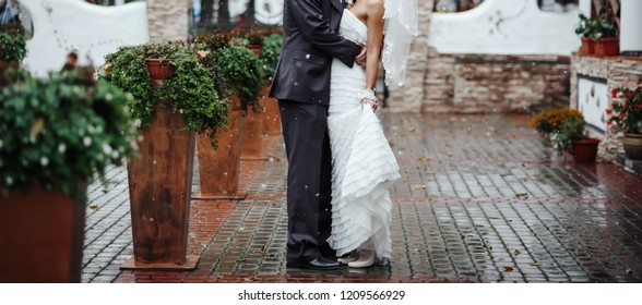 Bride and groom embracing. Wedding day atributes, suit, dress and bouquet
