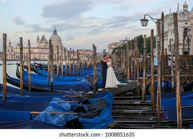 bride and groom embrancing  on dock near gondolas in Venice