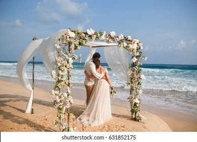 Bride and groom enjoying beach wedding in tropics,  wedding arch, ocean background