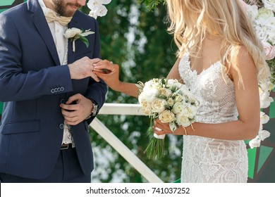 the bride and groom exchange rings
