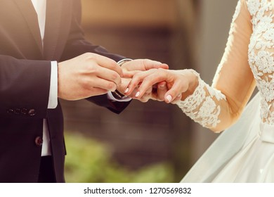 The bride and groom exchange rings during a wedding ceremony, a wedding in the summer garden