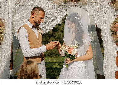 The bride and groom exchange rings on the wedding day during a ceremony under an arch with flowers. Loving young couple.