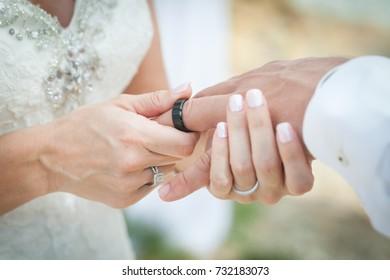 The bride and groom exchange rings in wedding day. The bride puts the ring on the groom. Photo closeup