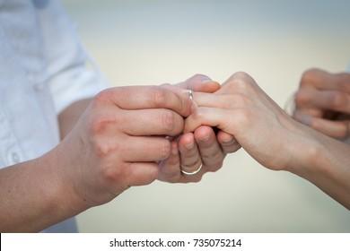 The bride and groom exchange rings in wedding day.  The groom puts the ring on the bride. Photo closeup