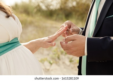 bride and groom exchanging wedding rings during ceremony