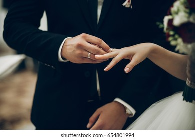 bride and groom exchanging wedding rings, putting on fingers during wedding ceremony in church. wedding couple