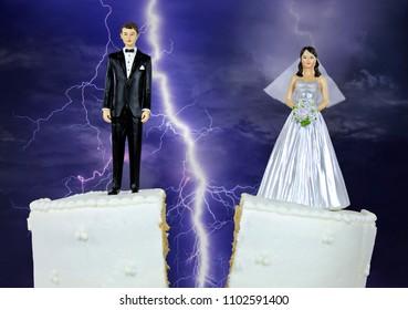 bride and groom figurine on split wedding cake with stormy lightning background