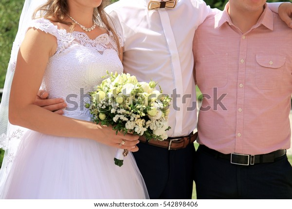 Bride and groom with friend posing in the park on the wedding day