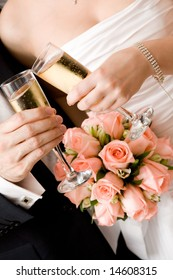 bride and groom with glasses of champagne and red rose bouquet