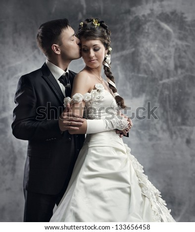 Bride and groom at gray grunge background. Wedding couple fashion shoot.