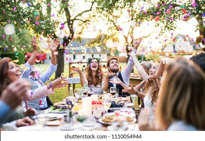 Bride and groom with guests at wedding reception outside in the backyard.