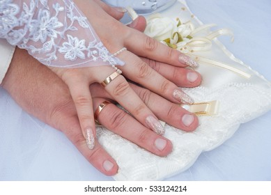 Bride and groom hand in hand on a cushion for the rings